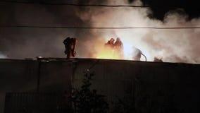 Brandbestrijder op een dak stock videobeelden