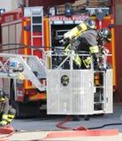 Brandbestrijder op kooi van brandladder Royalty-vrije Stock Fotografie