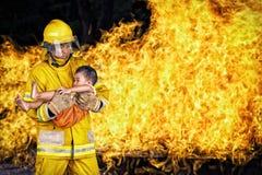 brandbestrijder , redt de reddingsbrandweerman een kind van brandincident Stock Foto's