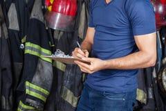 Brandbestrijder Writing On Clipboard stock afbeelding