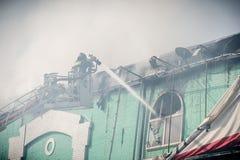 Brandbestrijders in actie het vechten, dovende brand, in rook Stock Foto's