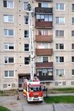 Brandbestrijders in actie, mensenuprise in telescopische boommand van brandvrachtwagen Flatgebouw op achtergrond Stock Afbeeldingen