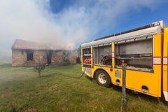 Brandbestrijders in actie met grote gele brandvrachtwagen Stock Foto