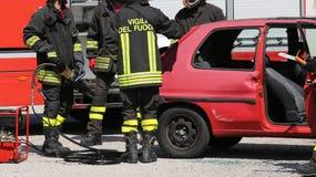 Brandbestrijders in actie tijdens een autoongeval Royalty-vrije Stock Foto's