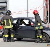 Brandbestrijders in actie tijdens het autoongeval Stock Afbeelding