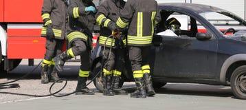 Brandbestrijders in actie tijdens het autoongeval Stock Fotografie