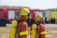 2 brandbestrijders in brandbeveiligingmateriaal en brandvrachtwagen backg Stock Foto's