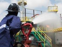 Brandbestrijders die brand met gedrukt water bestrijden tijdens opleidingsoefening Brandvechter die een rechte stoom weg bespuite stock afbeeldingen