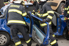 Brandbestrijders die de scherpe deuren verwijderen uit een autowrak Royalty-vrije Stock Foto