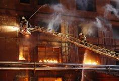 Brandbestrijders die een brand bestrijden Stock Foto's