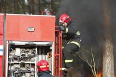 Brandbestrijders die een brand voorbereidingen treffen te doven stock afbeelding