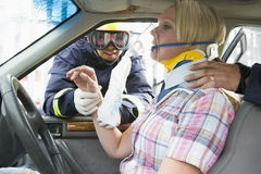 Brandbestrijders die een verwonde vrouw in een auto helpen Stock Afbeeldingen