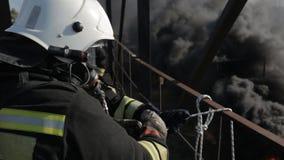 Brandbestrijders die het gasmaskerswerk dragen bij hoogte stock video