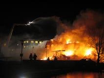 Brandbestrijders die uit brandend huis zetten. Stock Fotografie