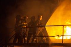 Brandbestrijders die volledige nevel gebruiken om een brand tijdens brandbestrijdingsoefening te doven stock foto's