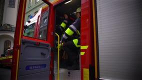 Brandbestrijders in het eenvormige krijgen in firetruck, die op een opdracht, gevaarlijke baan gaan stock footage