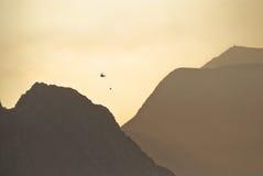 Brandbestrijdingshelikopter die boven bergen vliegen stock afbeeldingen