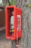 Brandblusapparaat in een rode doos in bijlage aan een boom wordt geplaatst die royalty-vrije stock afbeeldingen
