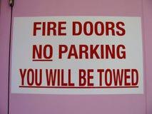 Branddörrar ingen parkering ska du vara det bogserade tecknet Royaltyfri Foto