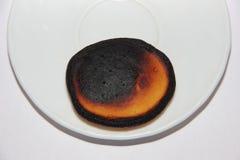 Brandde weinig pannekoek ligt op de rand van een witte plaat, die op een witte achtergrond wordt gevestigd Stock Foto