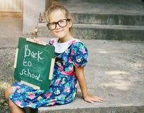 Bärande exponeringsglas för härlig flicka som rymmer den svart tavlan med ord tillbaka till skolan utomhus- stående Arkivfoto