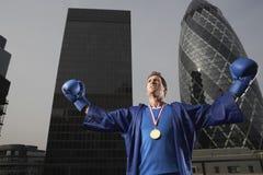 Bärande guldmedalj för boxare mot i stadens centrum skyskrapor Arkivfoton