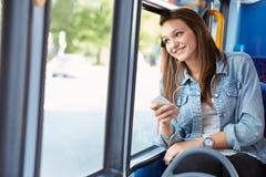 Bärande hörlurar för tonårs- flicka som lyssnar till musik på bussen Arkivbilder