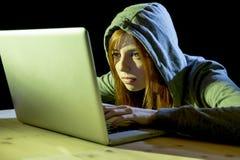 Bärande huv för ung attraktiv tonårig kvinna på begrepp för brott för cyber för cybercrime för dataintrångbärbar datordator Royaltyfri Foto