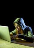 Bärande huv för ung attraktiv tonårig kvinna på begrepp för brott för cyber för cybercrime för dataintrångbärbar datordator Arkivbild