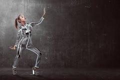 Bärande latexjumpsuit för kvinna som poserar över grungebakgrund Arkivbild