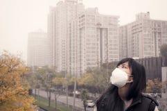 Bärande munmaskering för asiatisk flicka mot ogenomskinlighetsluftförorening Arkivfoto