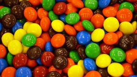 M&m candy lunettes texture background. Branded lunettes in different colors as green, yellow, orange, red, blue and brown stacked together, a bunch of candies royalty free stock image