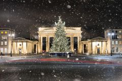 The Brandenburg Gate in Berlin with Christmas tree. The Brandenburg Gate in Berlin, Germany, during winter with Christmas tree and snowfall stock photos