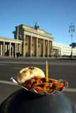 Brandenburg Gate and Berlin Curry sausage. One of Germanys typical and most popular meals, the Berlin Currywurst (sausage with curry sauce) in front of the most royalty free stock image