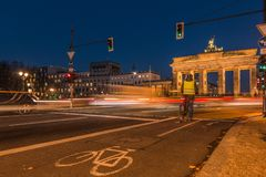 Brandenburg gate at night with cyclist and illuminated and bicycle path stock photo