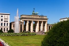 Brandenburger tor berlin. Fountain, green meadow with flowers and blue sky royalty free stock images