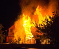 Brandend blokhuis bij nacht Heldere oranje vlammen en walm van onder het betegelde dak op donkere hemel, bomensilhouetten en royalty-vrije stock afbeeldingen