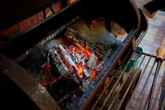 Brandend brandhout in de barbecue bij binnenplaats dicht omhoog Stock Afbeelding