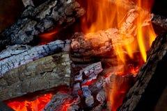 Brandend brandhout in de barbecue bij binnenplaats dicht omhoog Stock Foto's
