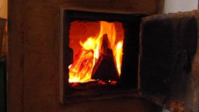 Brandend brandhout in oud rustiek baksteenfornuis met open deur stock footage