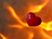 Brandend hart met vlammen tegen brandachtergrond Stock Foto