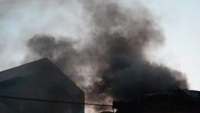 Brandend huis donkere zwarte rook die uit huis buiten in daglicht komen openlucht stock video