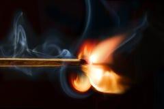 Brandend matchstick, zwarte achtergrond stock fotografie