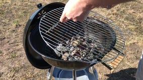 Brandend steenkolen en hout op een grillrooster Voorbereiding van steenkool voor barbecue stock video
