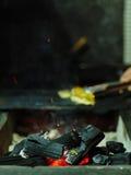 Brandende B-B-Q met brandhout Een mannelijke vleesstukken van handdraaien Gloeiend brandhout op een vage achtergrond De ruimte va Royalty-vrije Stock Afbeeldingen
