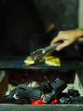 Brandende B-B-Q met brandhout Een mannelijke vleesstukken van handdraaien Gloeiend brandhout op een vage achtergrond De ruimte va Royalty-vrije Stock Foto's