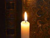 Brandende kaars en antieke boekachtergrond Stock Foto's