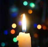 Brandende kaars op een achtergrond van Kerstmislichten Stock Foto