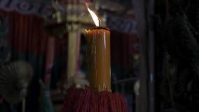 Brandende kaars op een zwarte achtergrond in de tempel stock footage