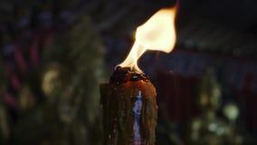 Brandende kaars op een zwarte achtergrond in de tempel stock videobeelden